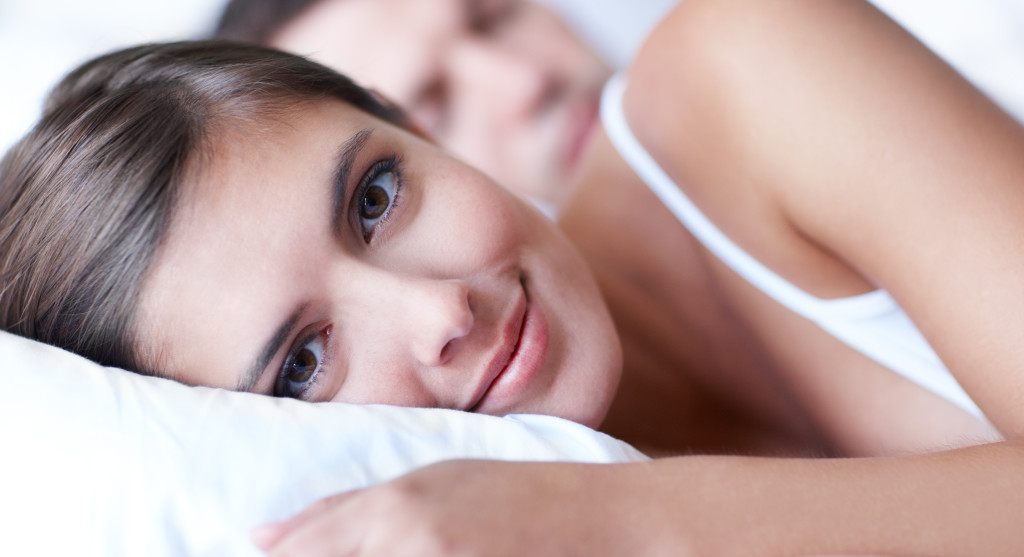 Portrait of an attractive young woman lying in bed while her partner sleeps
